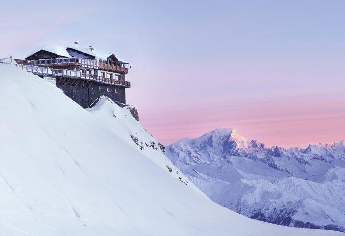 Belos tons de azul, rosa e lilás banham as montanhas cheias de neve dos Alpes Franceses, onde os visitantes podem desfrutar da vista em uns dos excelentes hóteis ao lado das pistas de esqui
